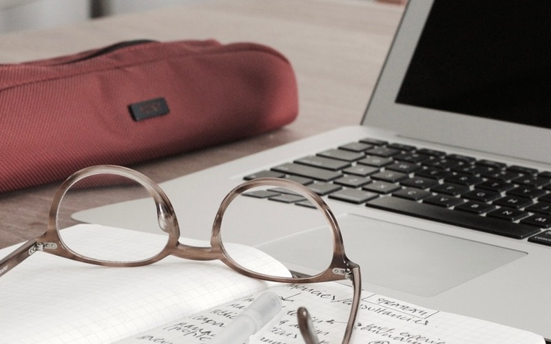 close shot of a desk with a computer, a pencil case and glasses on it