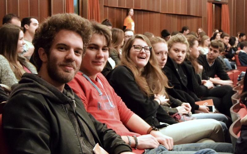 students sit in the auditorium, smiling at the camera