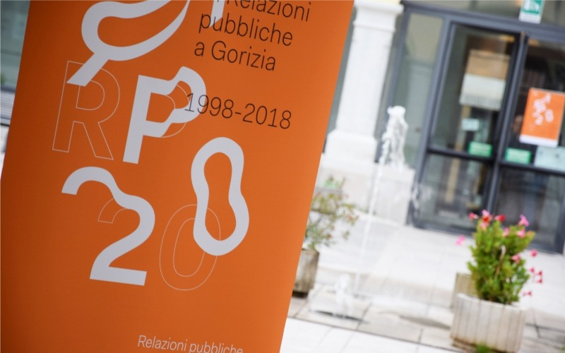 20 year anniversay leaflet with the university entrance in the background