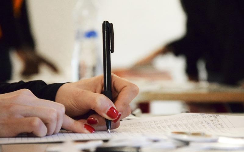 Immagine di persona che scrive su un foglio di carta